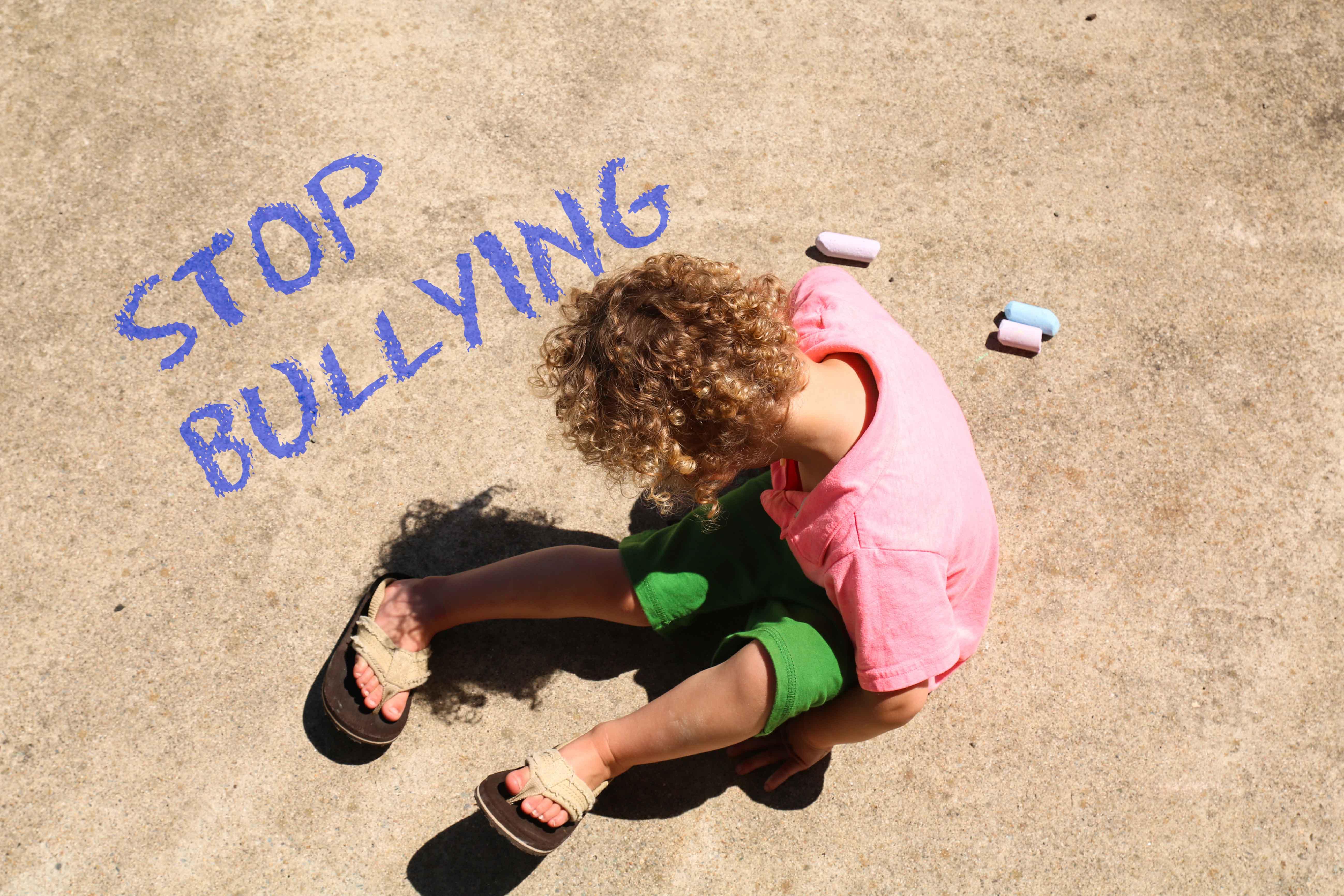 """Niño sentado en el suelo junto al mensaje escrito """"Stop Bullying"""""""
