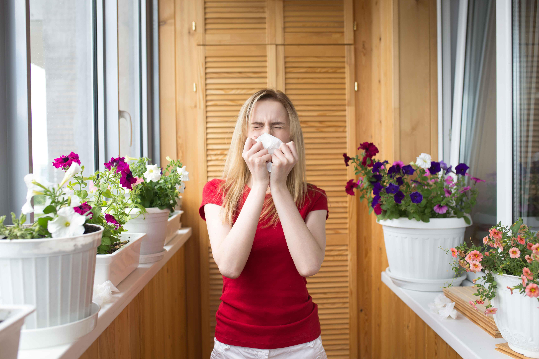 Chica estornudando en un balcón con plantas