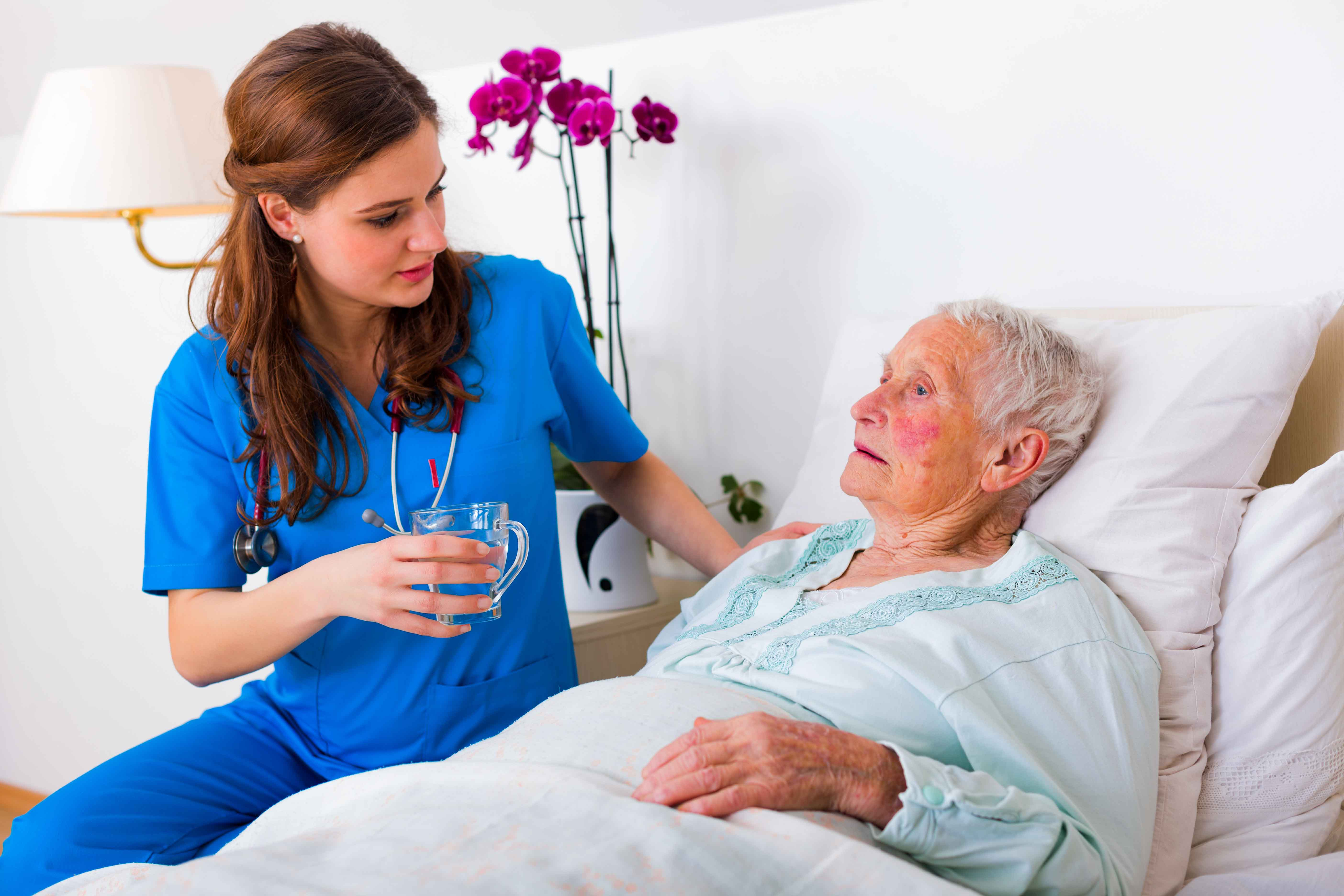 Sanitaria atendiendo a persona mayor con Alzheimer