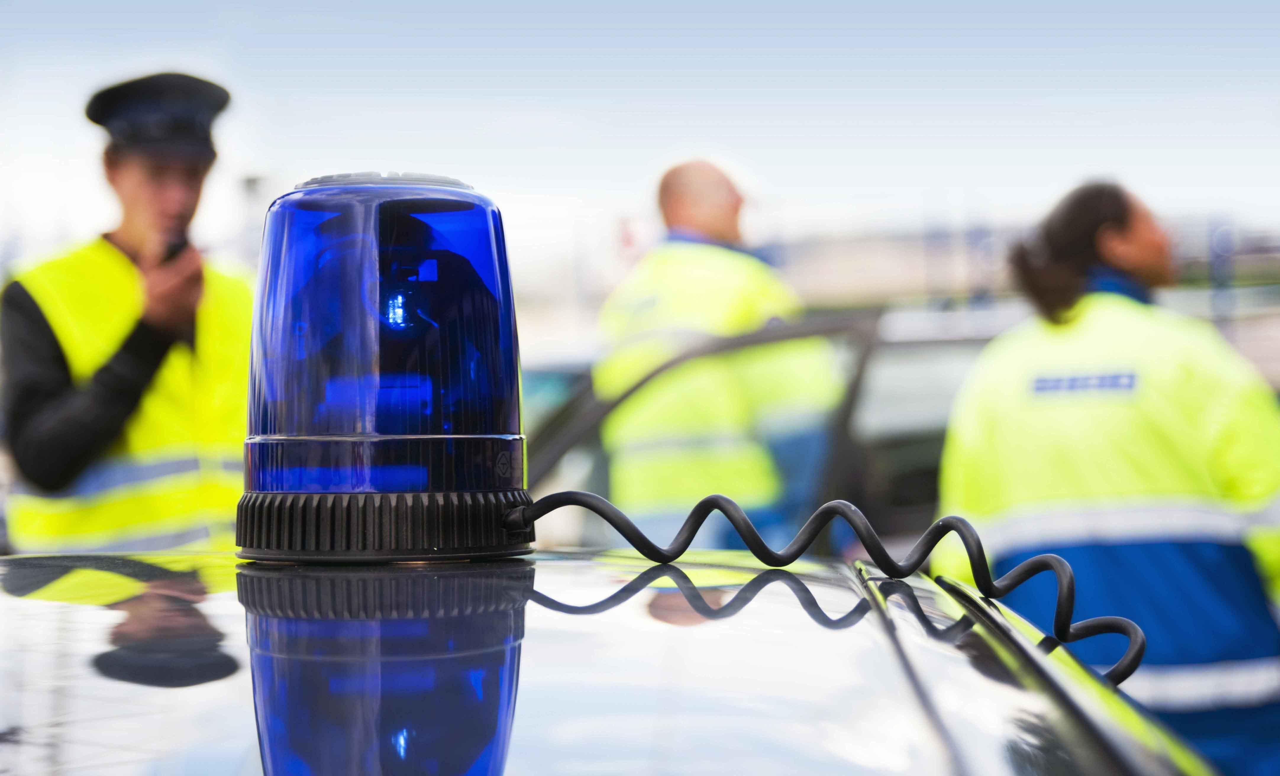 Policía de fondo tras sirena de coche