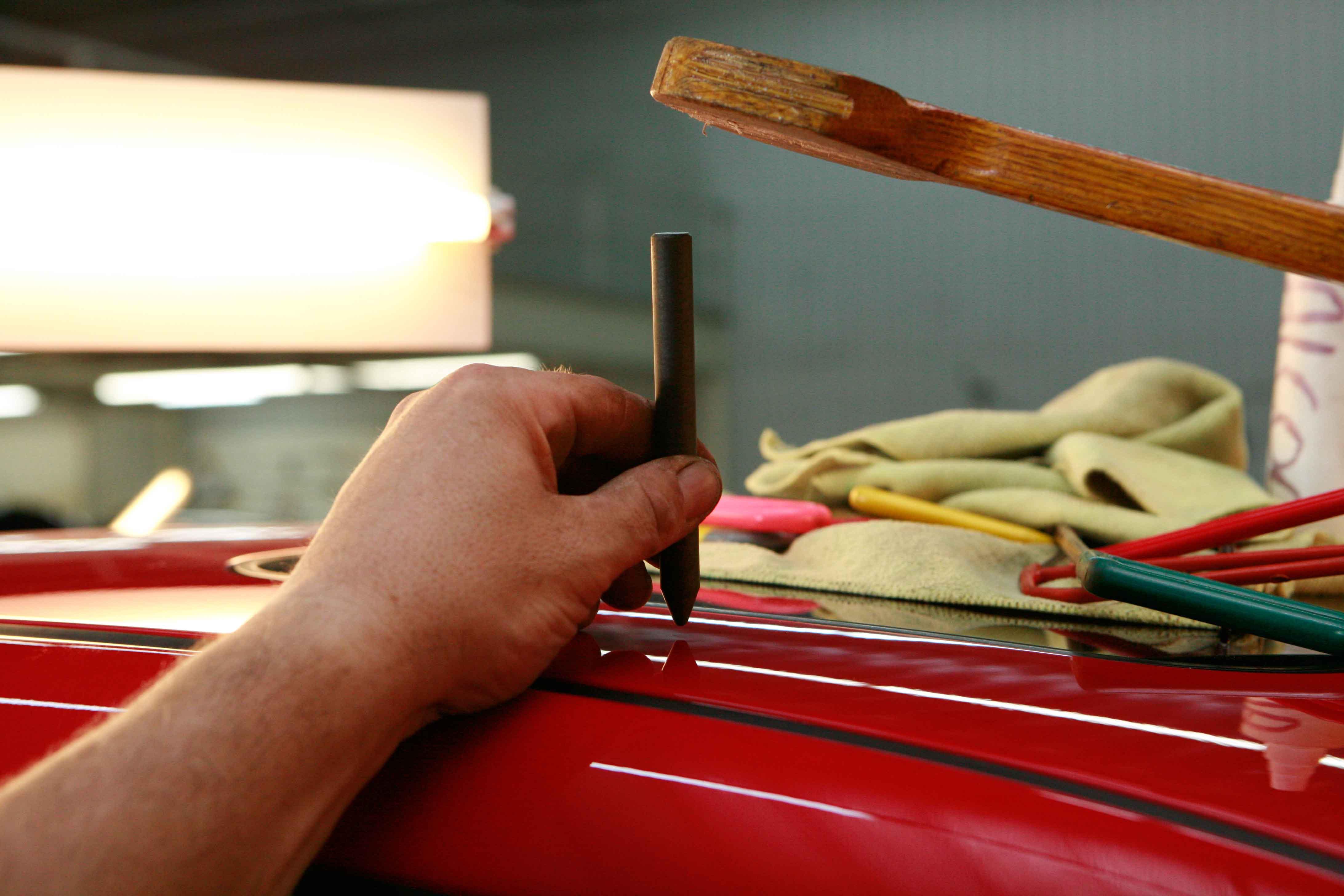 imagen de un mecánico arreglando chapa de coche