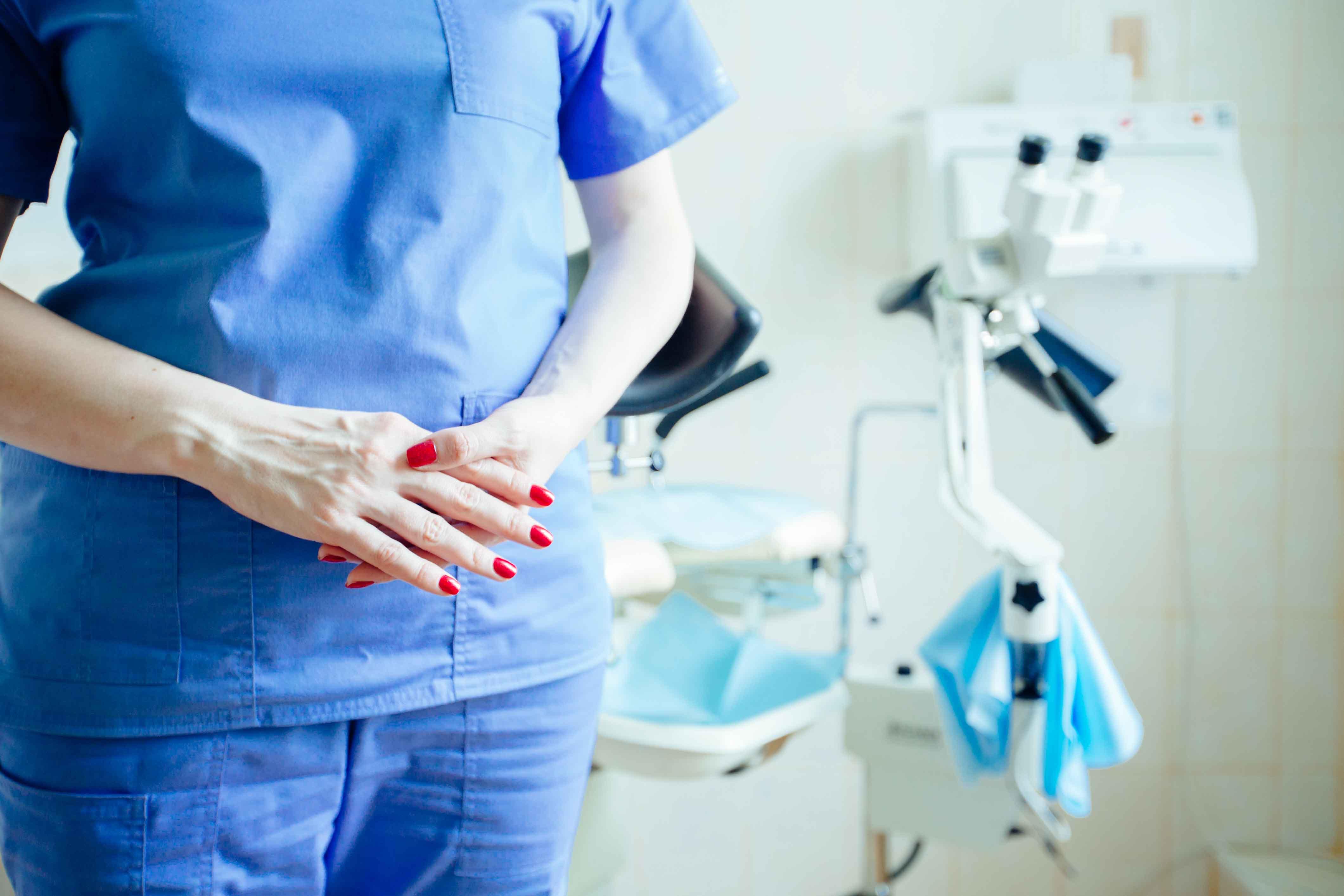 Doctora delante de silla de ginecología