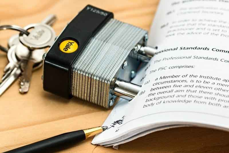 Trozo de un informe con un candado y unas llaves al lado