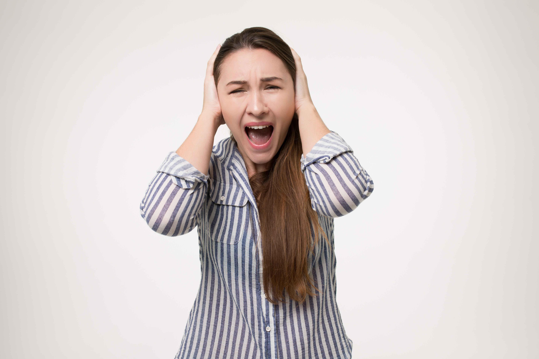 Chica gritando y tapándose los oídos