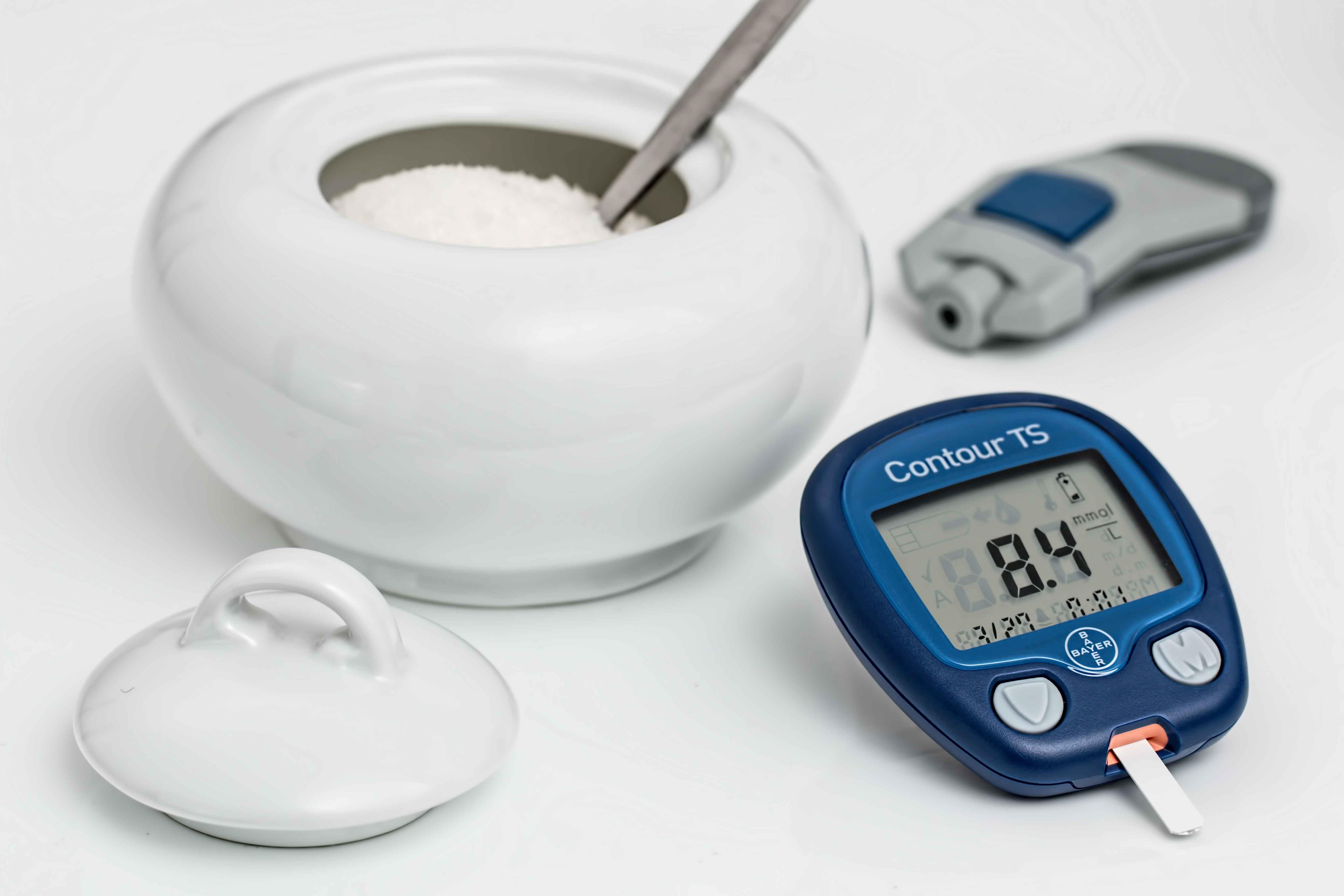 Medidor de azúcar en sangre junto a tarro de azúcar