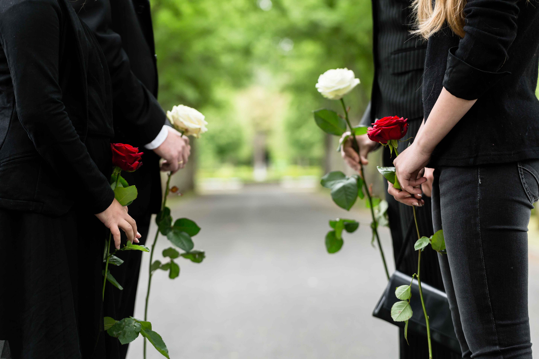 Familia de luto con rosas en la mano