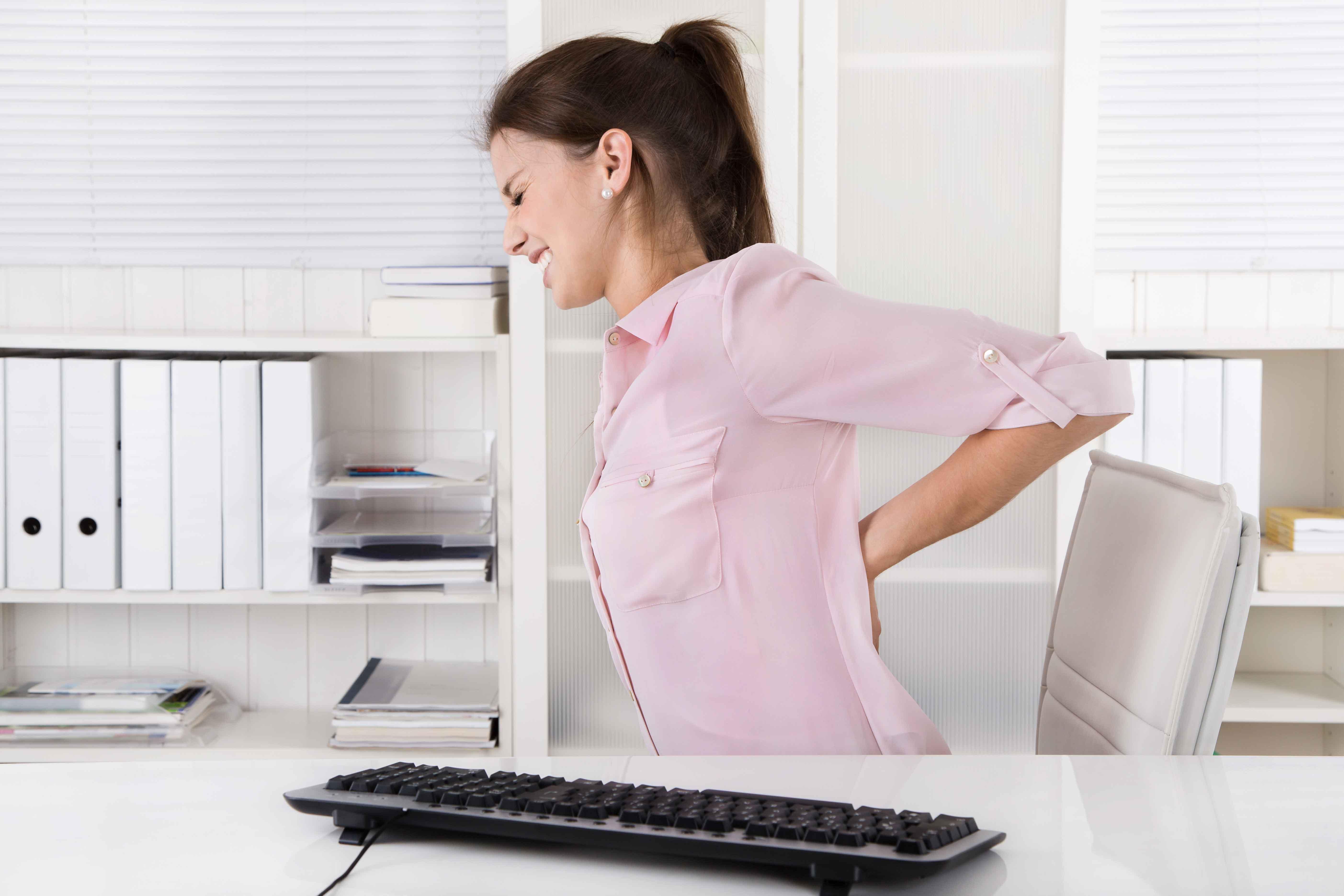Chica en silla de oficina con dolor de espalda