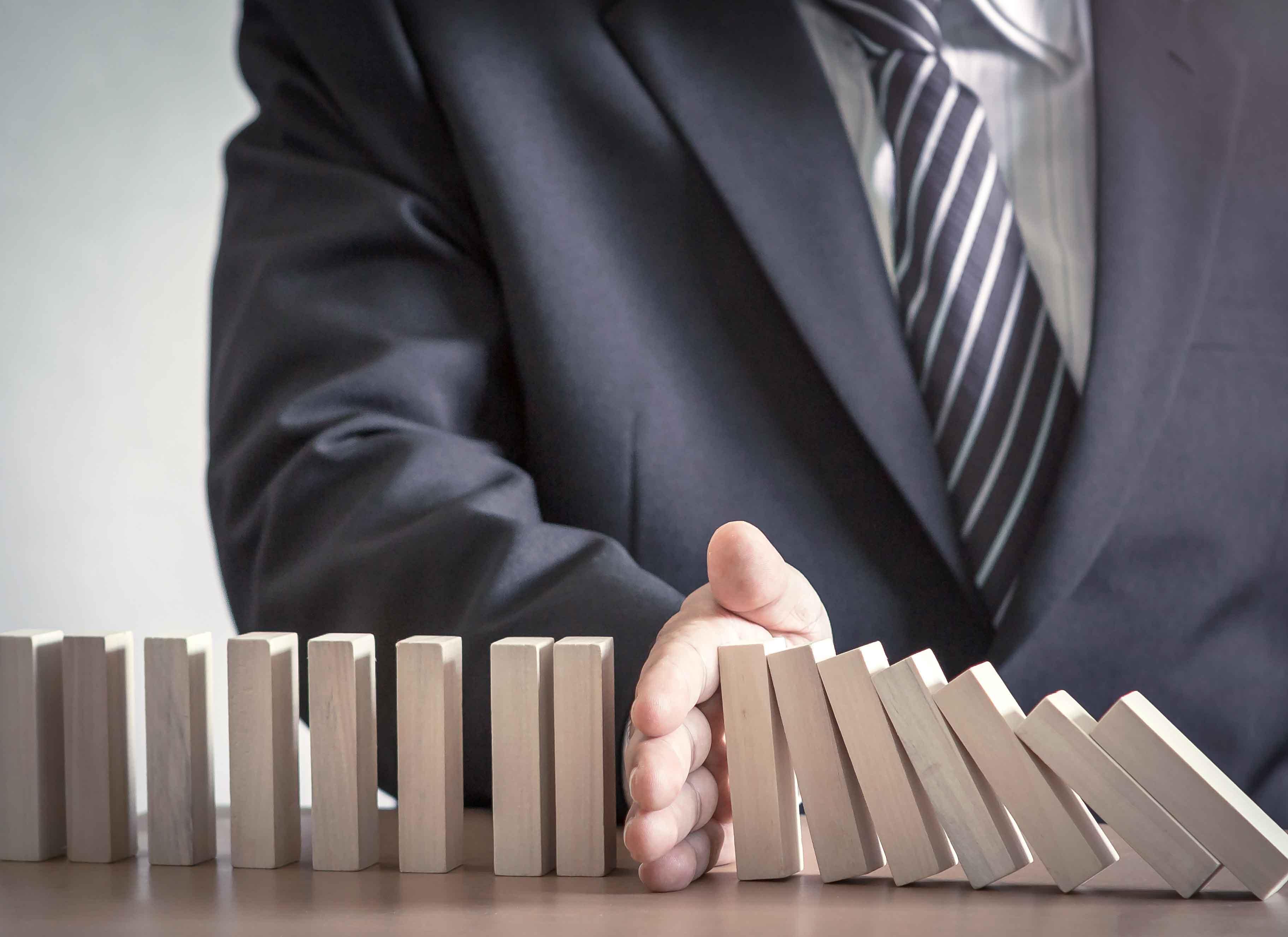 Persona sujetando piezas de dominó para q no se caigan en línea
