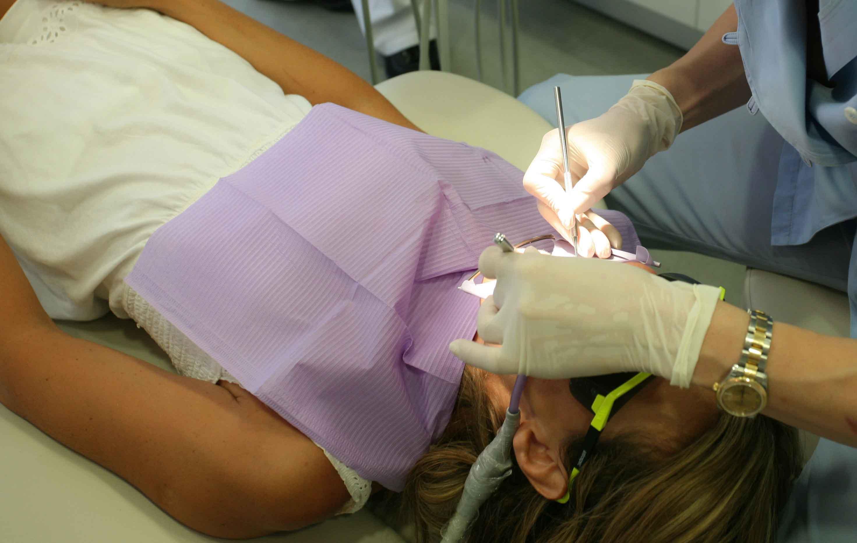 Mujer siendo atendida por odontólogo