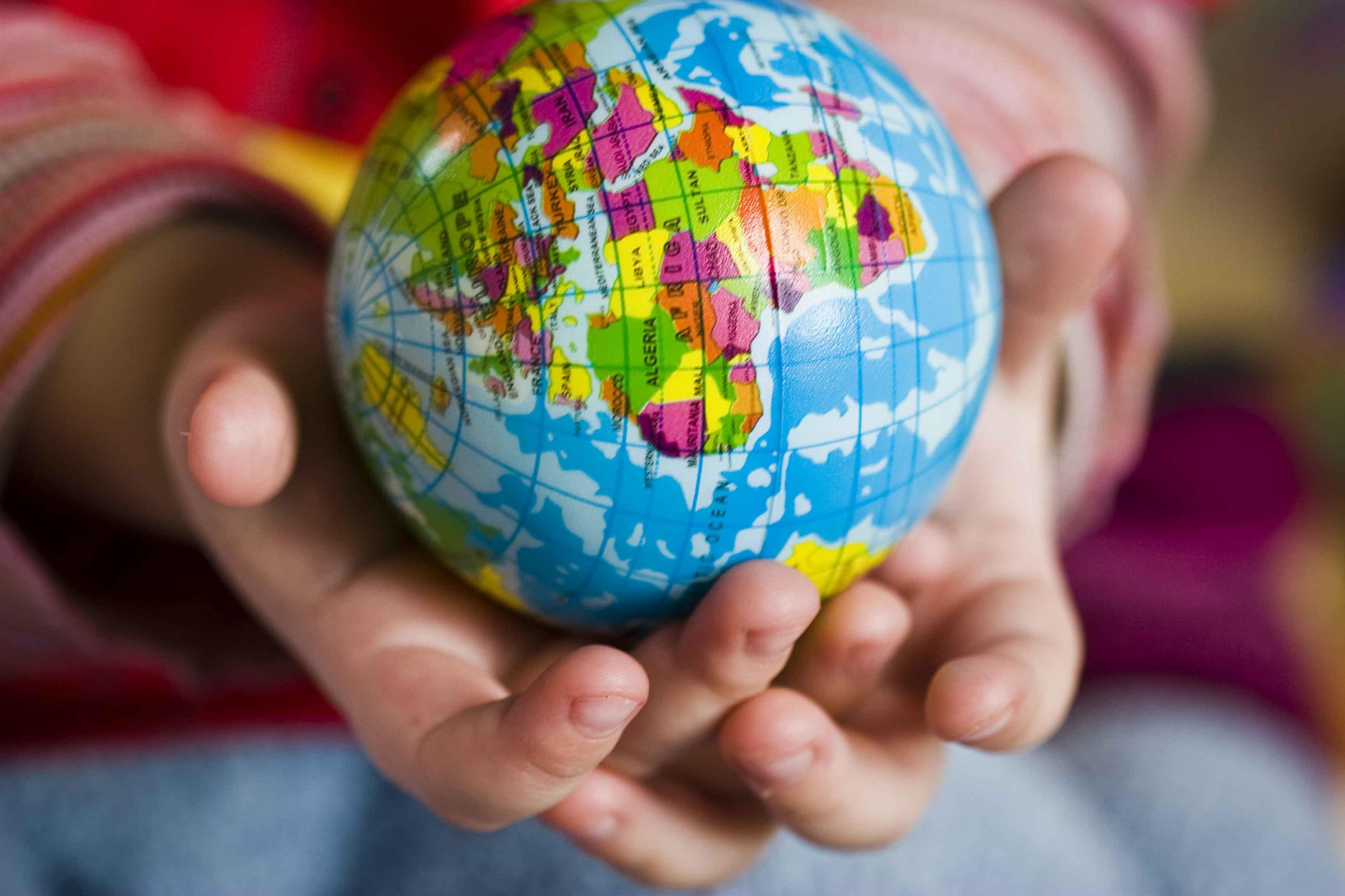 Manos de niño con bola del mundo en la mano