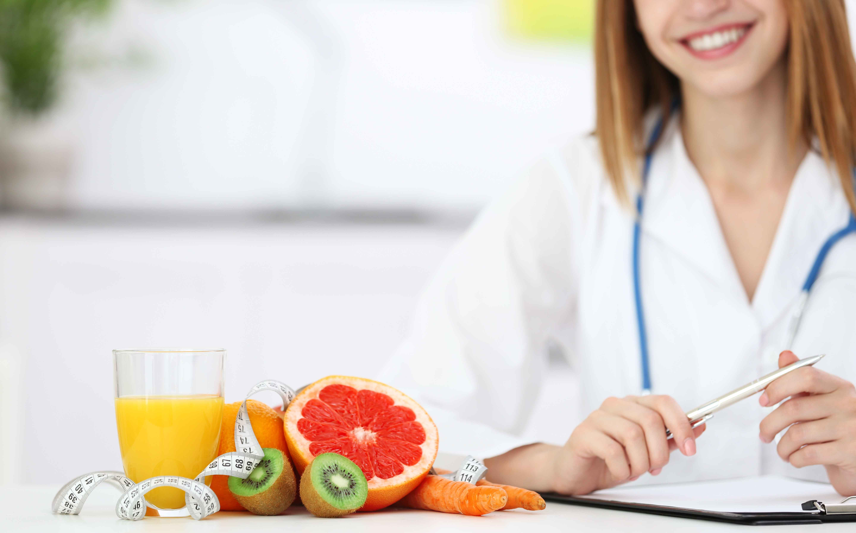 Doctora con plato de frutas y verduras delante