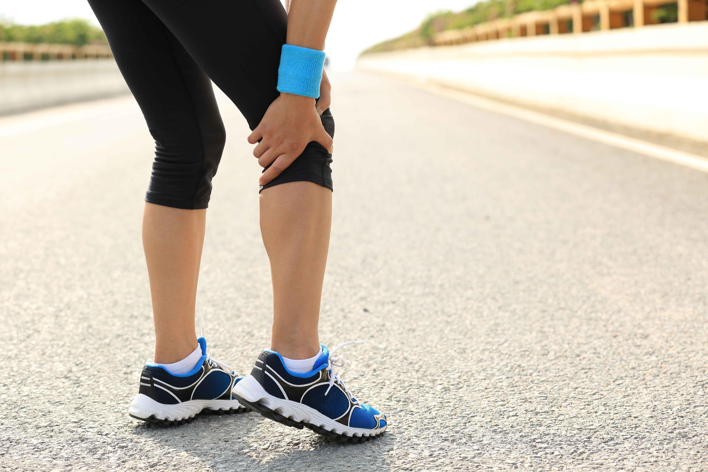 Runner parada en medio de la carretera tocándose la rodilla con dolor