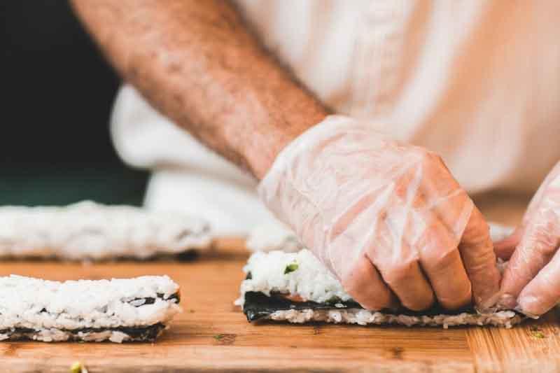 Manos de cocinero preparando sushi