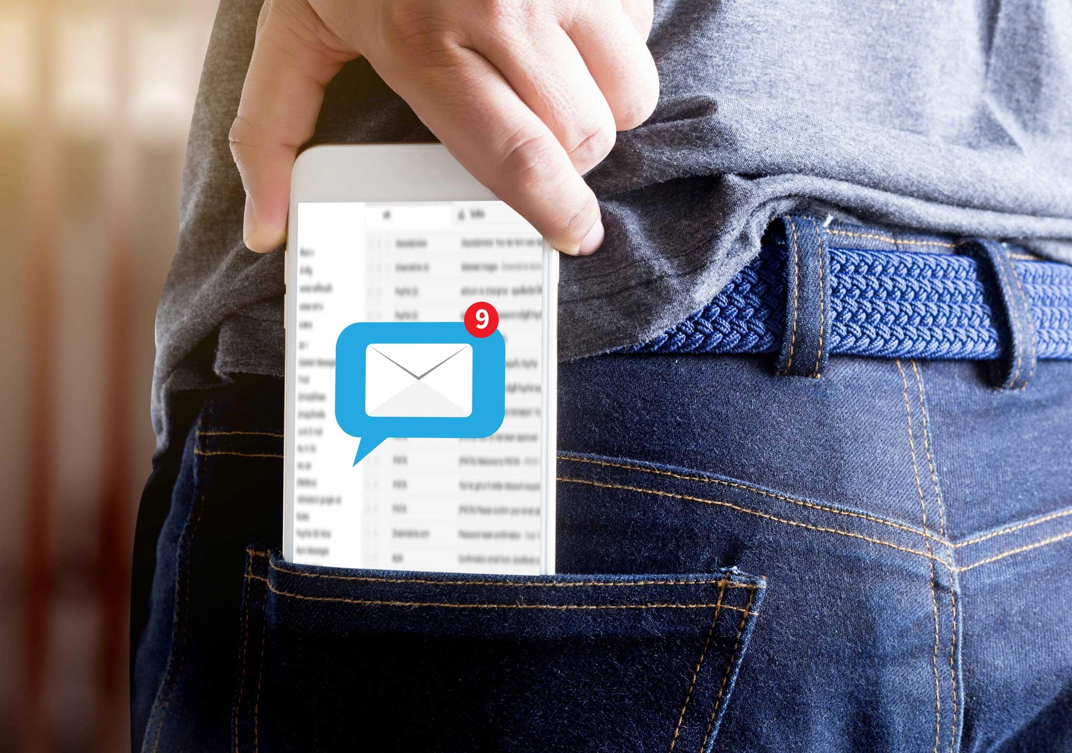 Móvil sacándose de bolsillo con notificación de nuevo mensaje