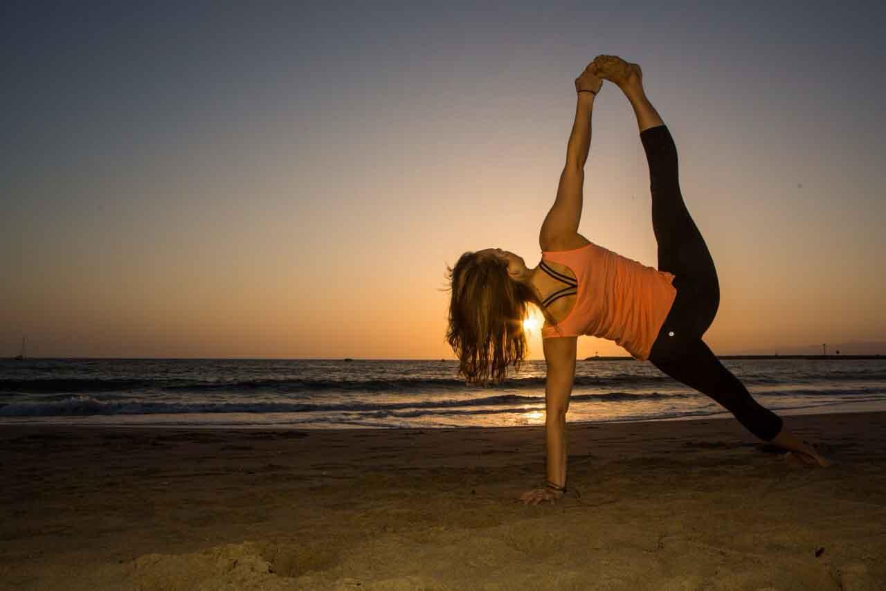 Chica practicando yoga al atardecer en la playa