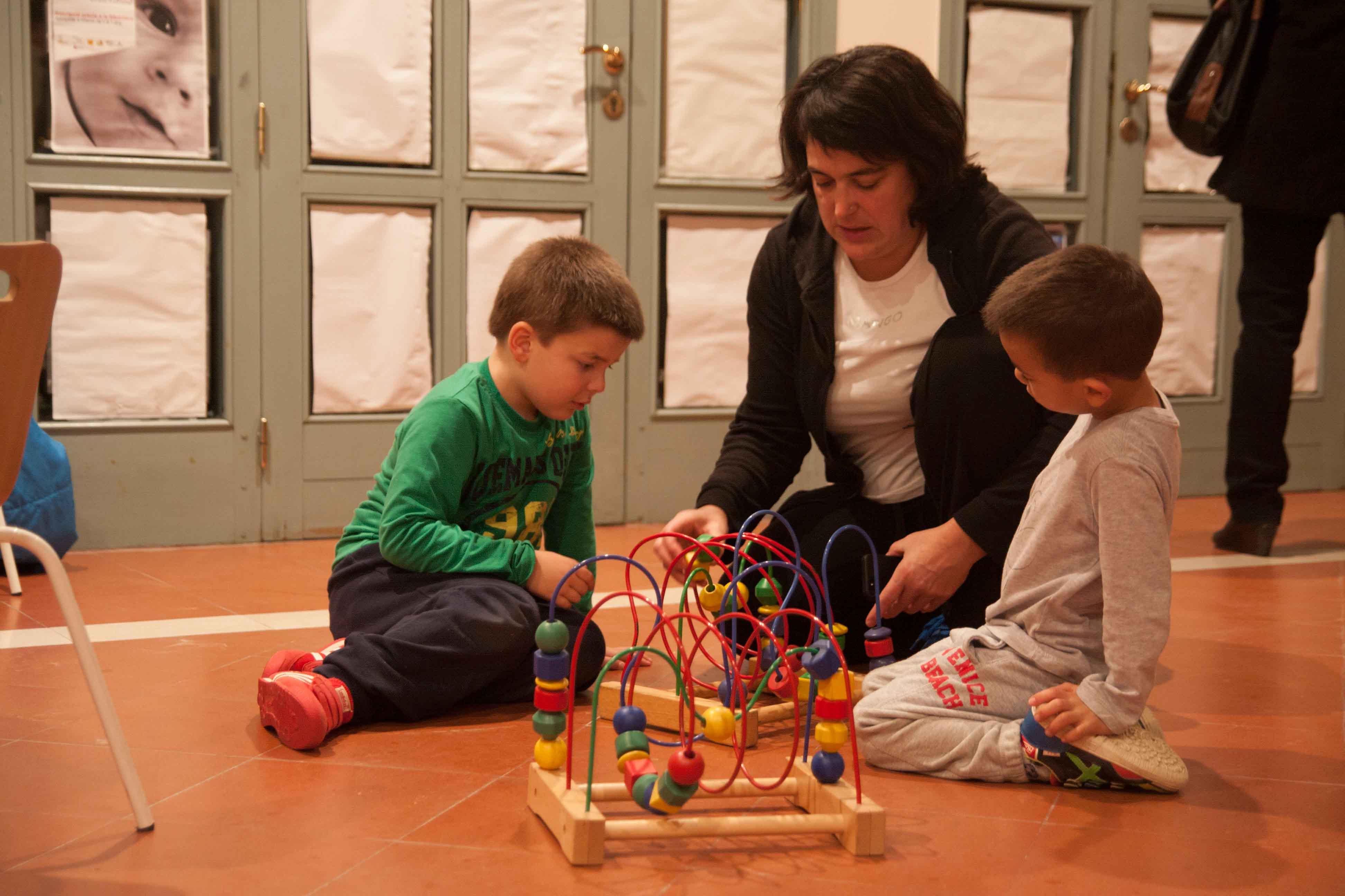 Maestra jugando con dos niños en el suelo de una ludoteca