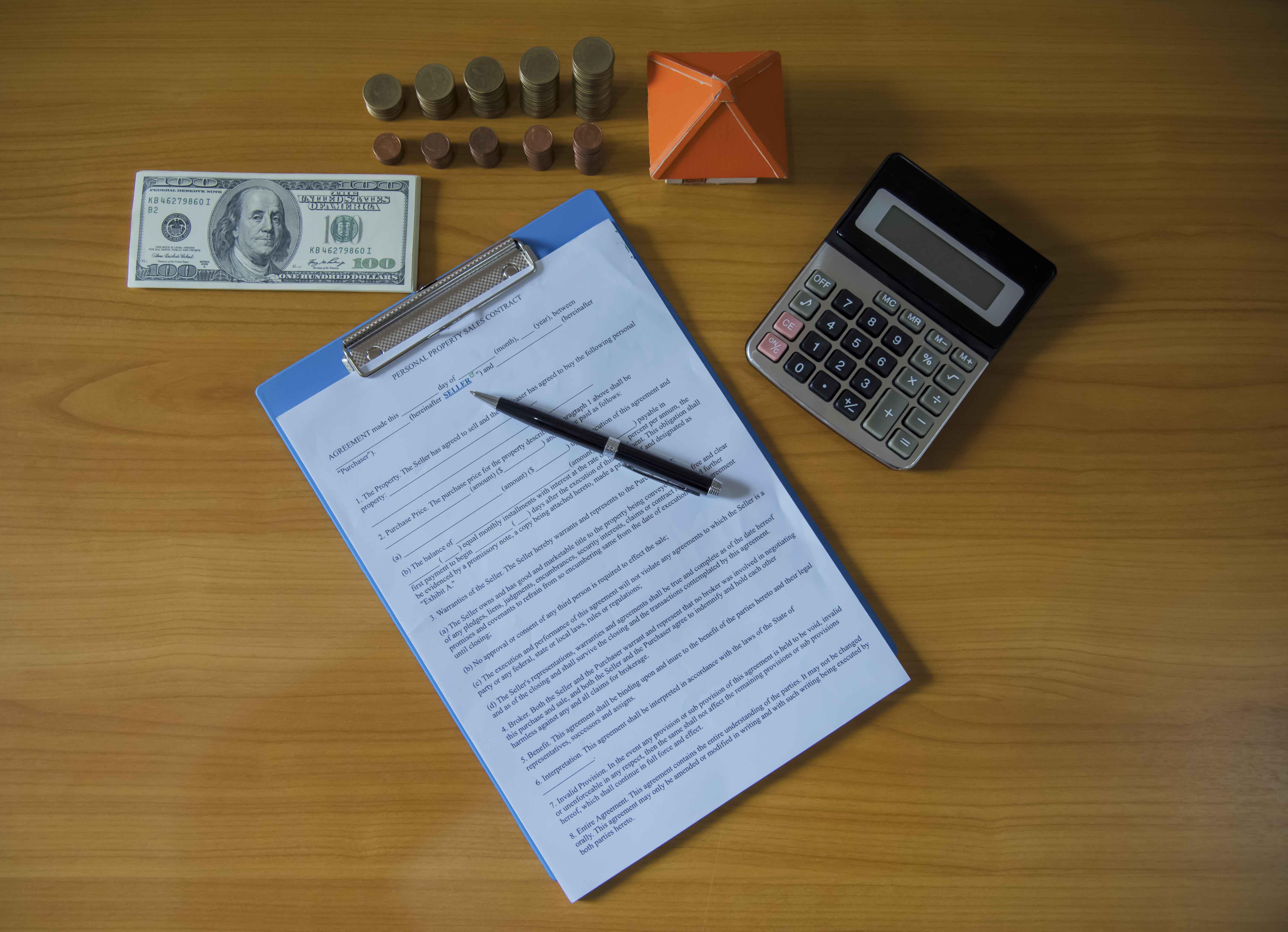 Contrato de imagen sobre mesa con dinero y calculadora