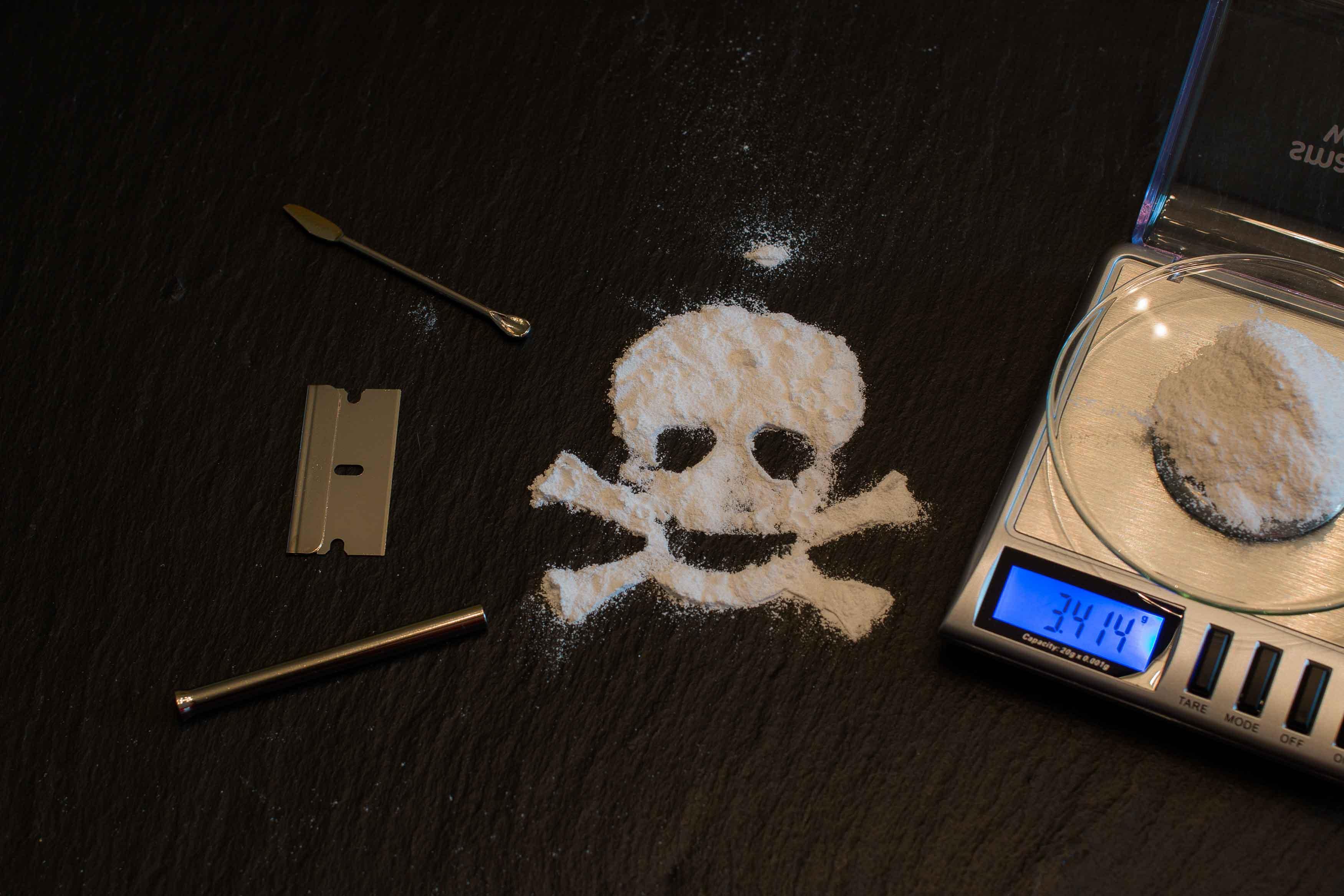 Báscula con coaína y cocaína dibujando una calavera