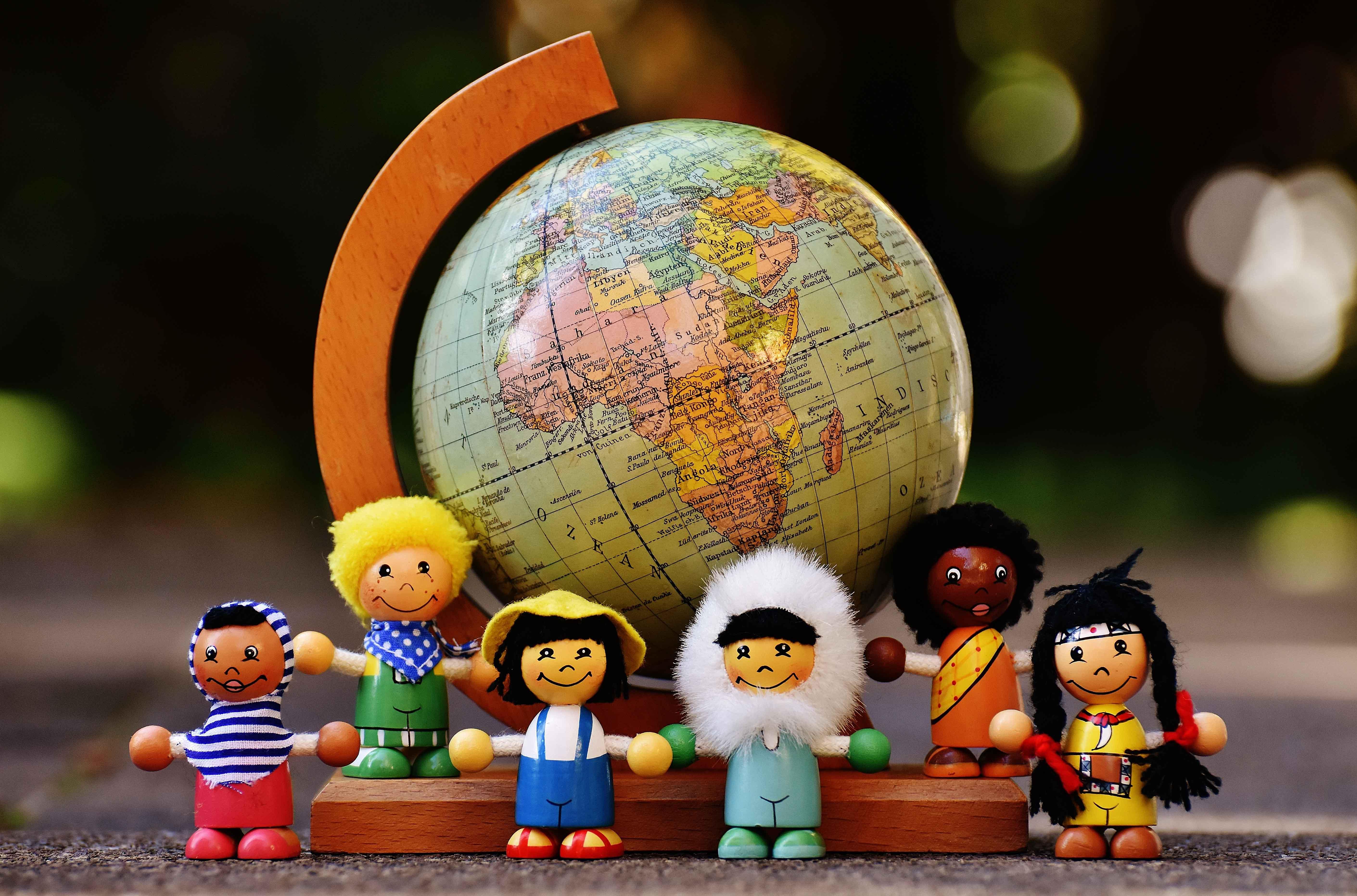 Figuras de gente de varias razas junto a bola del mundo