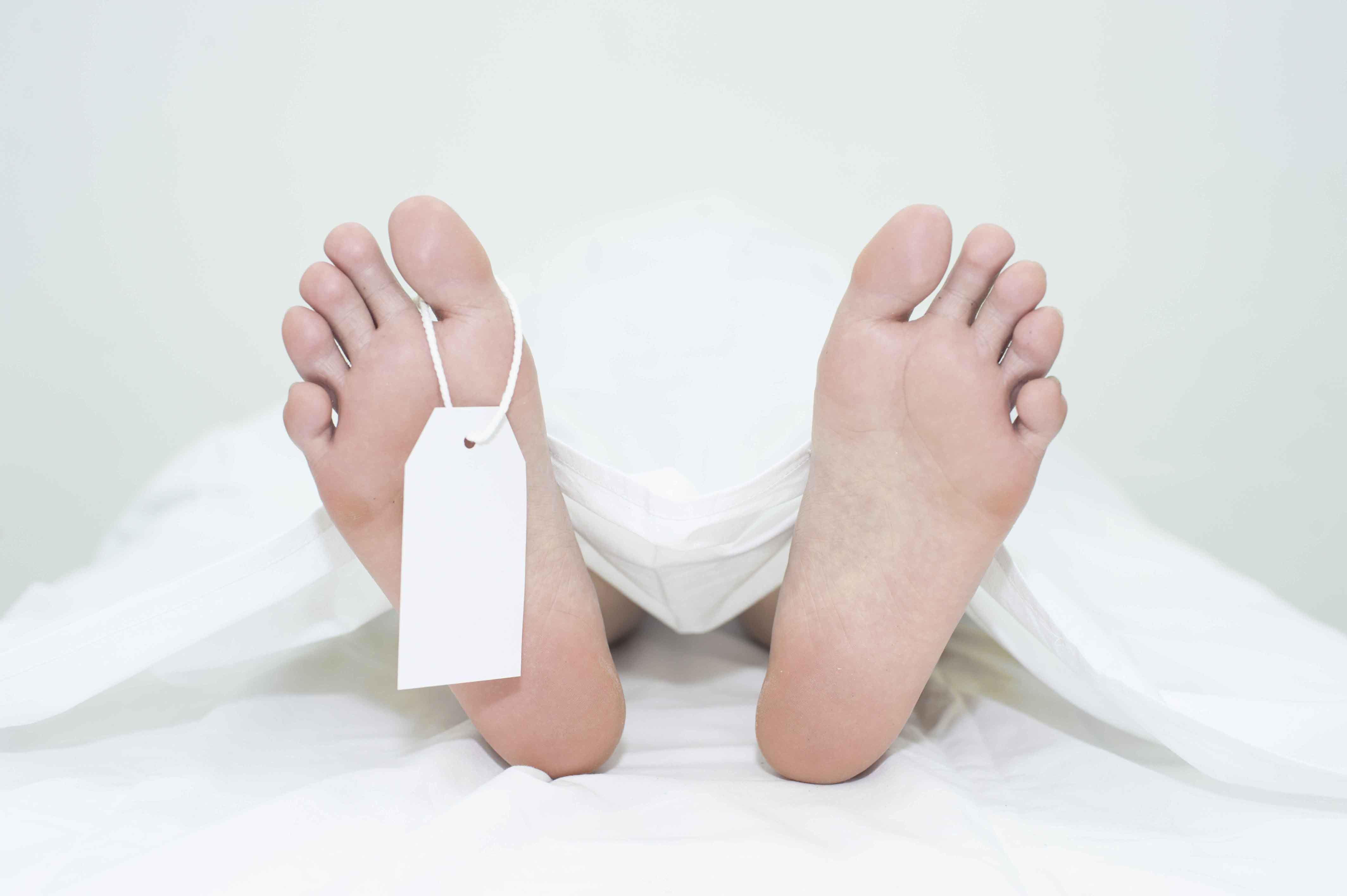 pies de un cadáver tapado con sábana